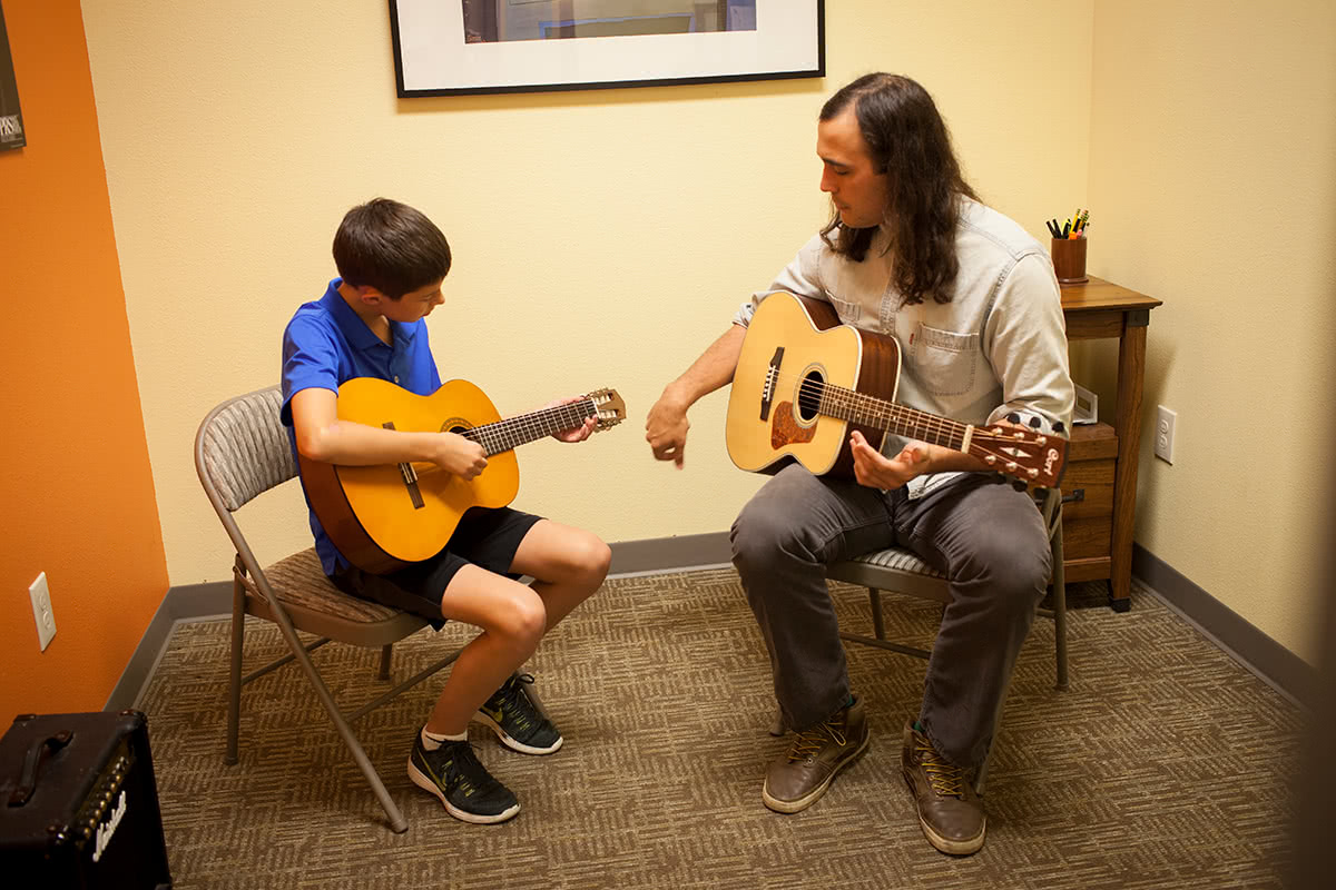 Child Learning to Play Acoustic Guitar
